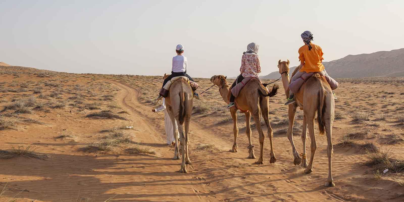 Family camel trekking in desert in Oman