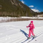 Winter scene of young girl cross country skiing in Norway, surrounded by mountains.