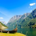 Viking boat in foreground in front of fjord and mountain scenery in Norway