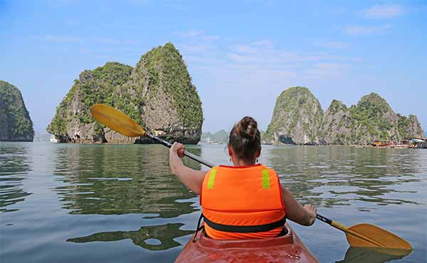 Young girl kayaking in Halong Bay Vietnam