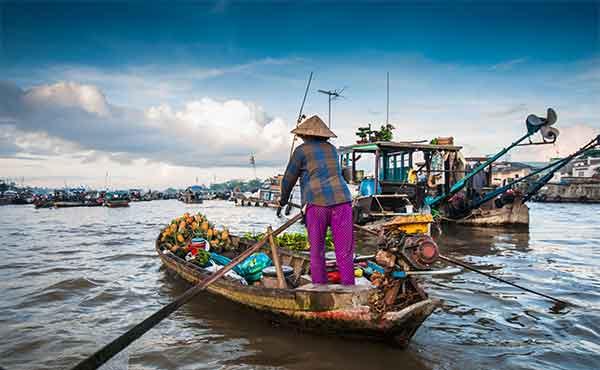 Vietnamese man selling produce in floating market at Cai Rang