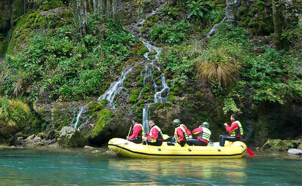 Group in inflatable raft on river with waterfall coming down cliff behind
