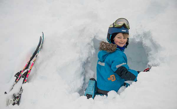 Young girl digging a snow cave during a skiing trip in Norway